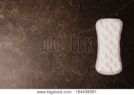 Women's white daytime hygiene pads on a dark marble background. Hygiene.