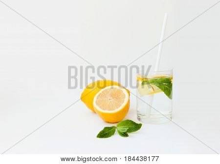 Homemade Lemonade With Water, Lemon And Mint Leaves In A Glass On A White Background.