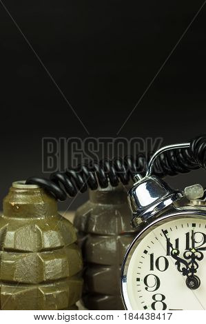 Grenade and old alarm clock. Timed bomb. The concept of terrorism