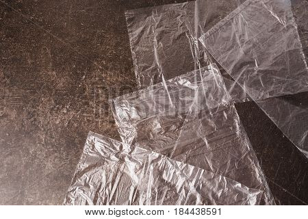 Cellophane bag on a dark marble background. Polute the nature. Eco concept with bag. Bag on table. Transparent bag
