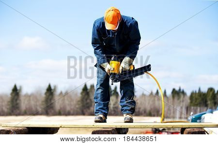 A 16 year old teenager wearing overalls steel toe work boots and gloves holding an industrial air nailer looking down at wood boards he's standing on