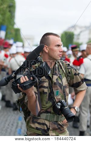 Paris. France. July 14 2012.Legionnaire photographer photographs parade on the Champs Elysees in Paris.