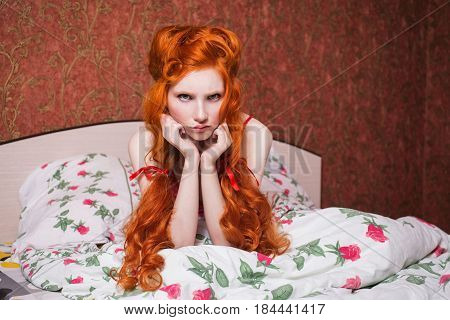 Woman with long red curly hair gathered into braids in nightgown in bed under a blanket. Red-haired girl with a pretty face pale skin blue eyes and bright unusual appearance in the bedroom
