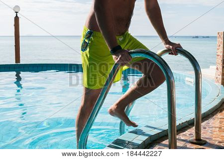Young guy in outdoor pool holds on handrails