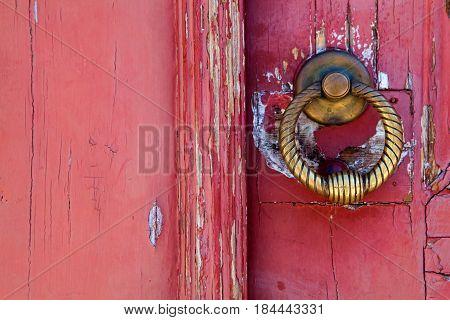 Brass knocker on old wooden door in Lisbon
