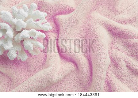 Beautiful white sea coral on the background of cotton terry pink towel crumpled by waves