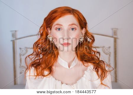 Portrait of a glamour woman with long red curly hair in a white glamour wedding dress with white pearl glamour earrings on her ears. Red-haired glamour girl with a pale skin blue eyes a bright unusual appearance in bedroom. Glamour model