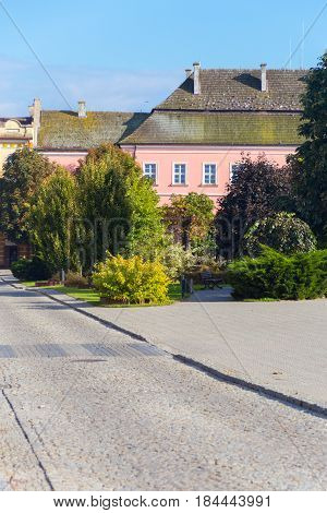 Traditional old town in Europe. Central square in Opatów, Poland with trees, cobbled street and old tenement house in pastel pink color. Photo taken on: September 26th, 2014