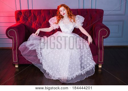 Elegant woman with long red curly hair in a white elegant vintage wedding dress with white pearl earrings on her ears. Red-haired elegant girl with pale skin blue eyes a bright unusual appearance sitting on a red couch. Elegant model