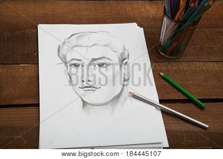 Drawn portrait of a man in black and white with colorful pencils on the wooden background