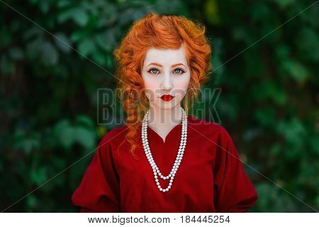 Cute woman with red hair and red slinky cute dress posing on a background of green leaves. Red-haired cute girl with pale skin and blue eyes with a bright unusual appearance with necklace of beads around her neck. Cute model