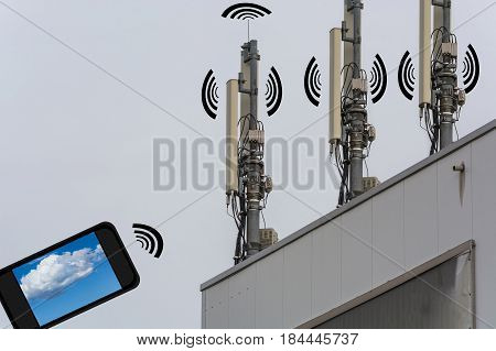 Antenna telecommunications tower on a roof. Wireless telecommunication concept home control by smartphone.