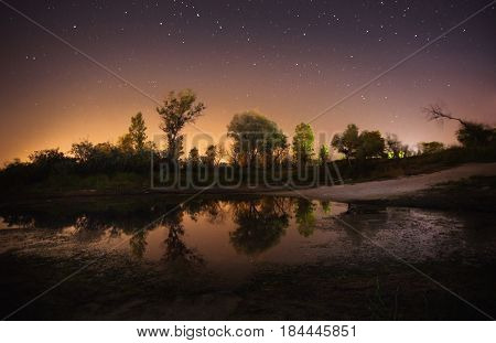 Beautiful night starry landscape. Stars reflected in the water at night. Astrophotography. Clear starry night sky. Slow shutter speed. The spectacular night sky. Scenic view at night.