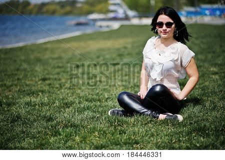 Brunette Girl On Women's Leather Pants And White Blouse, Sunglasses, Sitting On Geen Grass Against B
