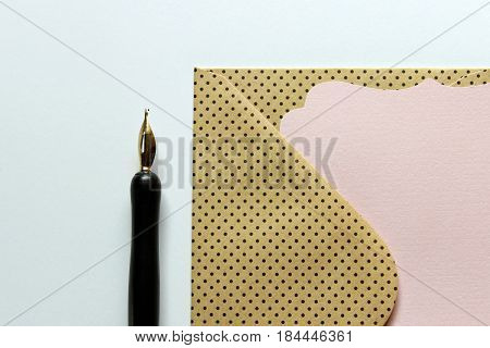 Calligraphy pen with pink notecard and polka dot envelope. Copy space.
