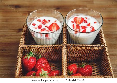 Glasses of Yogurt,Red Fresh Strawberries in the Rattan Box,on the Wooden Table.Summer Fruits.