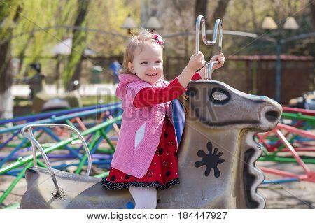 A Little Girl In A Red Dress Rides A Carousel, Riding A Deer