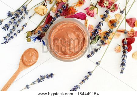 Jar of facial bentonite clay mask amidst dry holistic herbs, top view white wooden table. Soft focus on skincare mud.