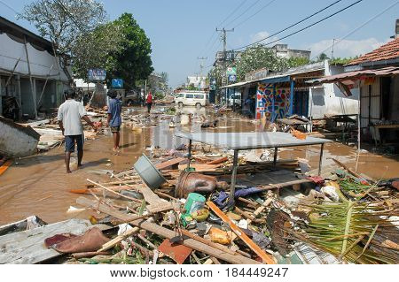 Hikkaduwa Sri Lanka - 26 December 2004: people walking on the debris after the tsunami at Hikkaduwa in Sri Lanka