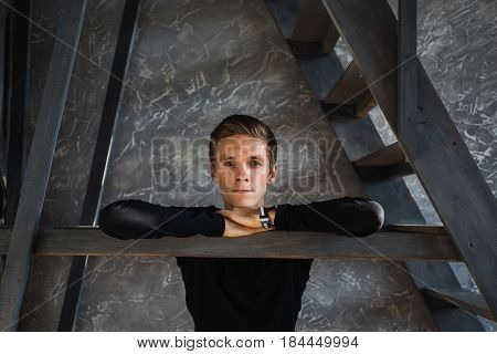 A young guy in a black shirt with a clock on the hand in the dark room with natural light. Emotional portrait. Bright display of emotion. Conceptual photography. The talented actor.