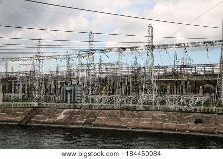 High voltage power transformer substation near the pond