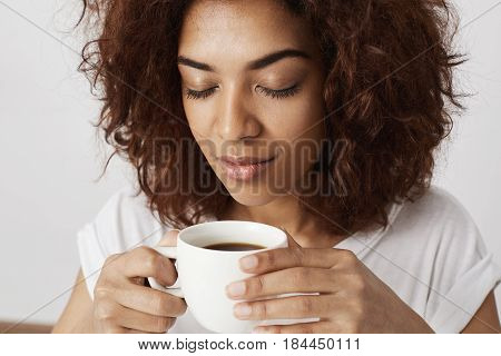 Close up photo of beautiful african girl holding cup smelling coffee with closed eyes.