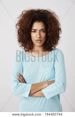 Displeased beautiful girl looking brutally at camera with crossed arms. White background