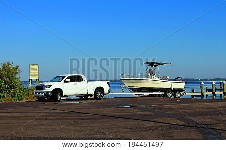 Vans with trailers and boats disembarking in an area located near a jetty