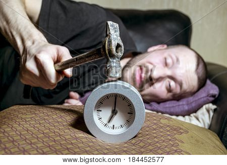 A man awake is trying to break the annoying alarm clock in the morning