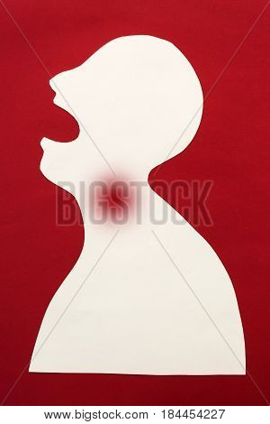 concept of human disease diagnosis and pain localization on silhouette - contour of abstract male man with opened mouth and sore spot in the throat, isolated on red background, top view, flat lay