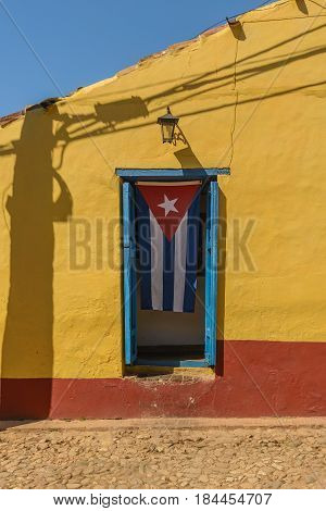 Cuban flag on yellow house   in the UNESCO World Heritage city center of Trinidad Cuba.