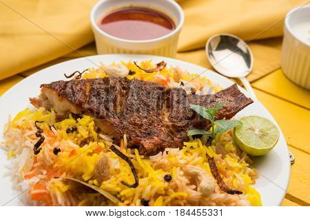 Fish Biryani or fish Rice - Popular Indian non-vegetarian recipe made of fish marinated with Indian spices fresh herbs and cooked with Basmati rice, selective focus