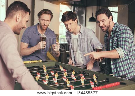 Table football. Friends spending time together in pub. Guys having fun while playing table football. Men drinking beer