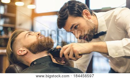 Young man sitting in a barbershop while barber trimming the beard