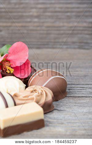 Delicious chocolate pralines on wooden background, fine luxury dessert