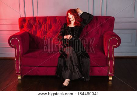 Beautiful vampire girl with red hair and natural make-up and pale skin. A woman vampire in a black retro dress sitting on a red couch. Model vampire posing in studio. The unusual appearance. Insidious wicked witch vampire woman.