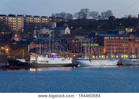 STOCKHOLM SWEDEN - APR 30 2017: Boats at the quay in central stockholm in the evening buildings in the background April 30 2017 in Stockholm Sweden