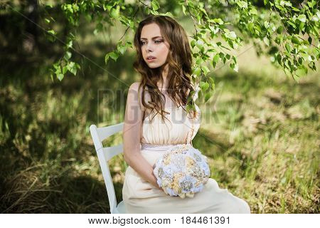 Beauty portrait of a very pretty elegant young girl. Doll appearance. Elegant woman with brown hair in a pink wedding dress on nature near the wedding decor. Long hair. Natural light. Elegant model posing in nature