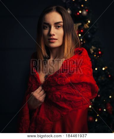 beautiful woman red cloak with red flowers roses in studio. Woman Red Riding Hood. Dramatic and fantastic shootingfashionable toning. Like a princess. With Christmas tree on the background