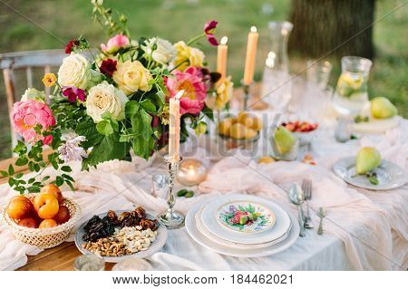 picnic, summer, holiday concept - beautiful table setting at the green lawn with tree, openwork white tablecloth, colorful summer bouquet of peony and roses, fruits, candlesticks, glassware, lemonade