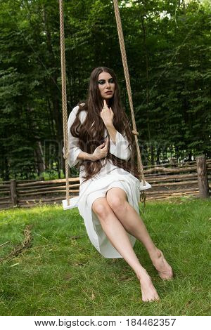 Young girl with long hair in a white dress is riding a rope swing in the forest. Folk style.