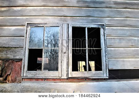 Broken window to abandoned house, trees in reflection