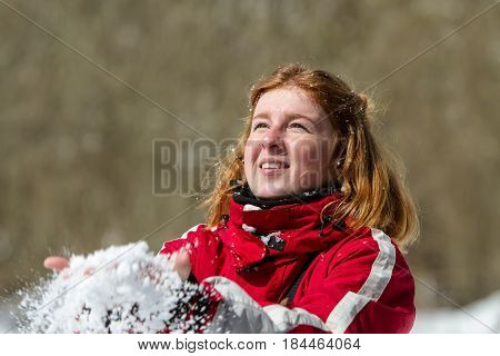 A young red-haired girl in a red jacket holding snow in her hands and throwing snow up.