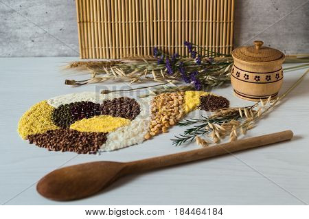 Placer of grains and cereals in form of horn of plenty. Wooden solt shakie with a lid and wooden spoon. Bunches of dried oats, wheat ears and poppy seeds.