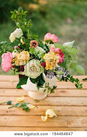 bouquet, holidays flower, gifts and floral arrangement concept - white vase of beautiful yellow and white roses, pink charming peon, carnations, shoots of wild rose, wooden table on green background