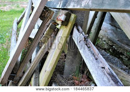 Many wooden fence pieces leaning against a wall.