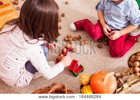 Children aggregate nuts in a toy train and learn to count sitting on the floor in kindergarten. Freight train concept