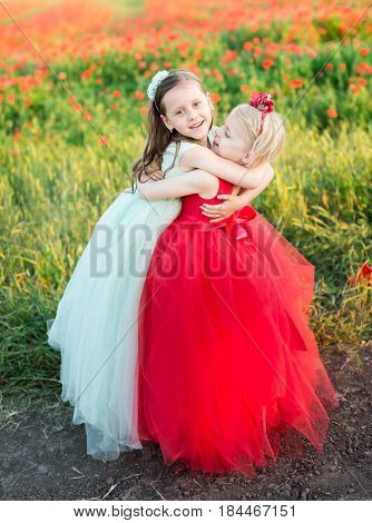 girl, childhood, fairytale and summer concept - the embrace of two little friends, one girl, in a blue dress, the second a blond in a red dress, standing in front of a blooming field of poppies