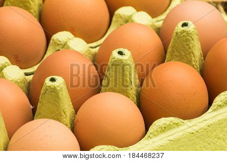 Freerange fresh raw eggs in recycled paper egg cartons or on the straw.