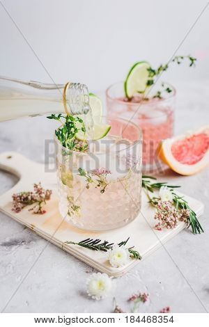natural alcoholic cocktail with herbs and cut lime for summer party on stone desk background